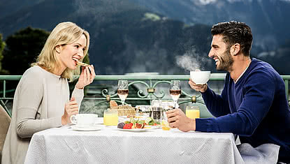 couple having breakfast with a view of the Zillertal mountains in the STOCK Resort