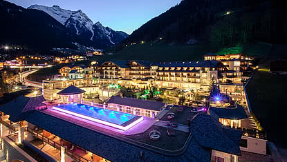STOCK resort exterior at night in the Zillertal, overlooking the outdoor sports pool